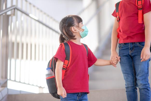 I fratelli asiatici della scuola primaria vanno di pari passo. sorella e ragazza con zaino dietro la schiena. inizio delle lezioni. primo giorno d'autunno.