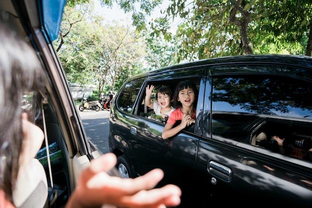 Fratelli asiatici che agitano le mani dalla finestra e viaggiano in auto