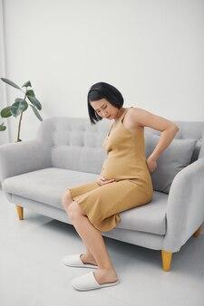 Giovane mamma femminile ammalata asiatica che tocca la vita e che tiene il grande bambino della pancia all'interno aggrottando le sopracciglia