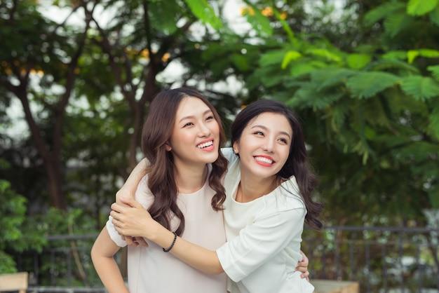 Sorelle asiatiche che si abbracciano e sorridono nel parco.