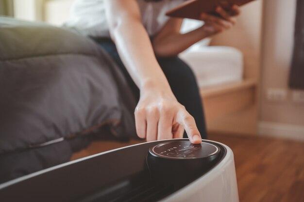 Donna asiatica assonnata che prova a premere un pulsante sulla macchina portatile del purificatore d'aria in una camera da letto