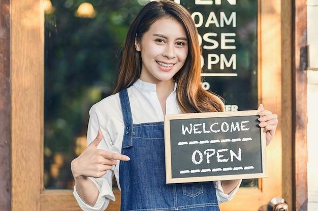 Il proprietario di una piccola impresa asiatica tiene le mani e mostra la lavagna con il segno di benvenuto aperto
