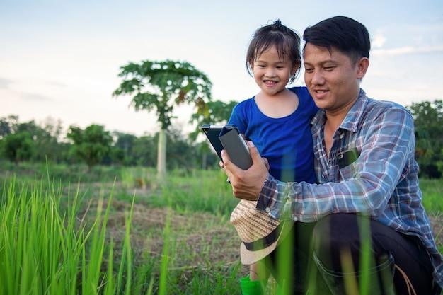 Padre asiatico contadino intelligente con la figlia bambina felice utilizzando la tavoletta digitale all'aperto nell'azienda agricola biologica di famiglia.