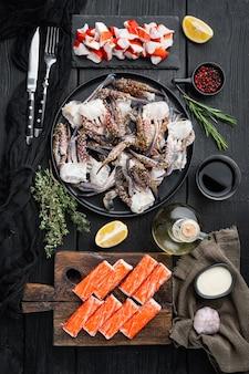 Insieme asiatico del surimi dello spuntino, sulla tavola di legno nera della tavola, laici piana di vista superiore