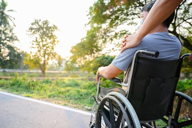 Figlio asiatico camminando con il padre disabile in sedia a rotelle nel parco aiutare il padre disabile spingendo una sedia a rotelle