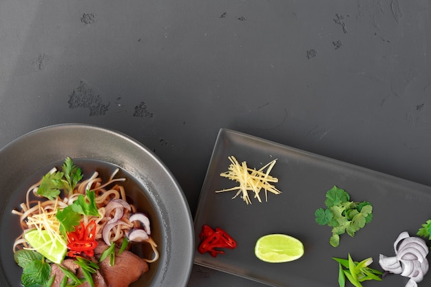 Zuppa asiatica ramen con carne di maiale e tagliatelle iserved su sfondo grigio vista dall'alto