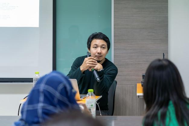 Altoparlante o conferenza asiatica con l'abito casual che dà il discorso di fronte alla stanza che presenta