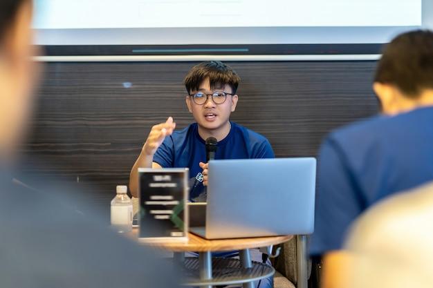 Altoparlante asiatico o lezione con tuta casual che dà il discorso di fronte alla stanza che presenta