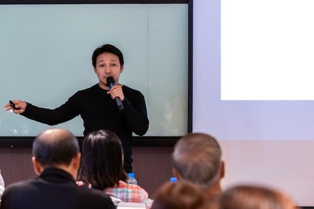 Altoparlante asiatico o lezione con tuta casual sul palco davanti alla sala che presenta