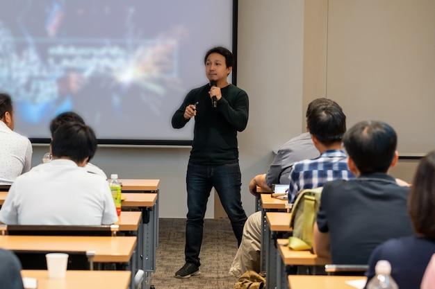Altoparlante asiatico con abito casual sul palco davanti alla stanza