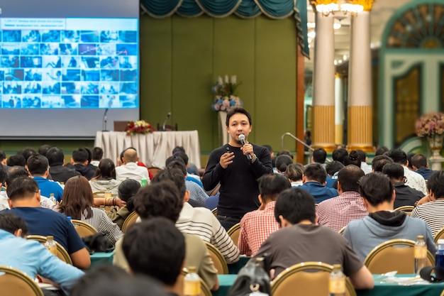 Speaker asiatico con tuta casual in piedi e dando la conoscenza con il pubblico nel conf
