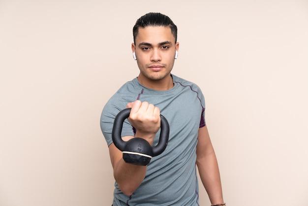 Uomo asiatico di sport isolato su beige che fa sollevamento pesi con kettlebell