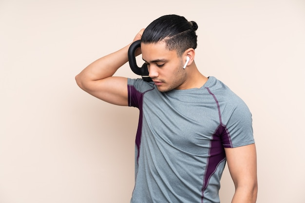 Uomo asiatico di sport isolato sulla parete beige che fa sollevamento pesi con kettlebell
