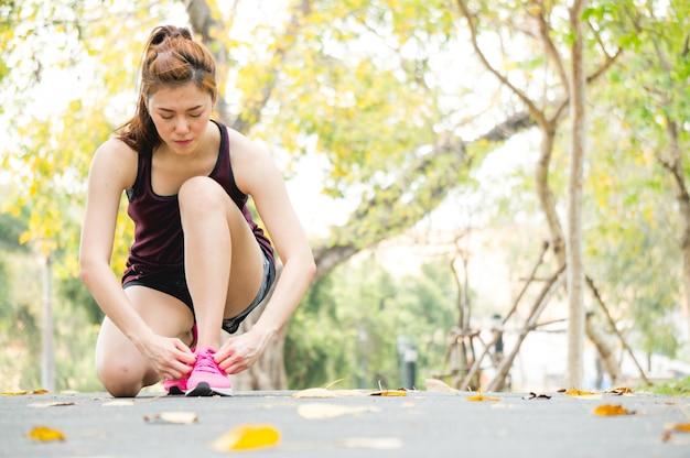 La donna asiatica di sport lega il laccio delle scarpe in parco durante pareggiare / correre