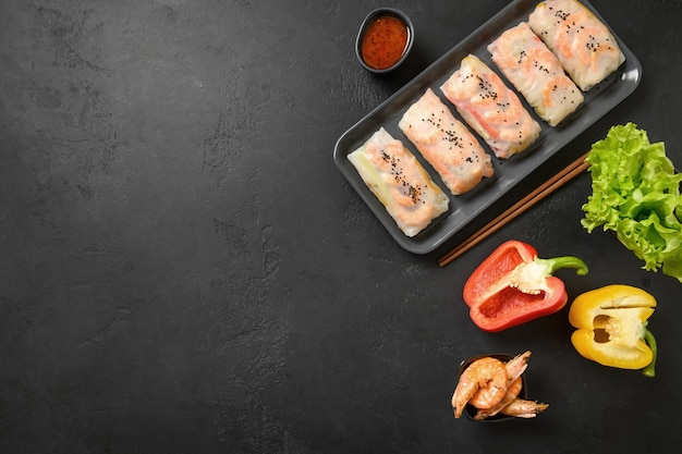 Involtini primavera asiatici con verdure colorate, gamberi avvolti in carta di riso su sfondo nero con spazio di copia. vista dall'alto.