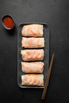 Involtini primavera asiatici con gamberi con salsa piccante su sfondo nero.