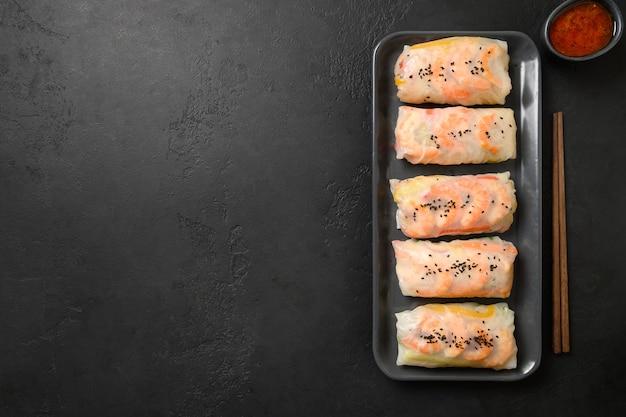 Involtini primavera asiatici con gamberi con salsa piccante avvolti in carta di riso su sfondo nero con spazio di copia. vista dall'alto.