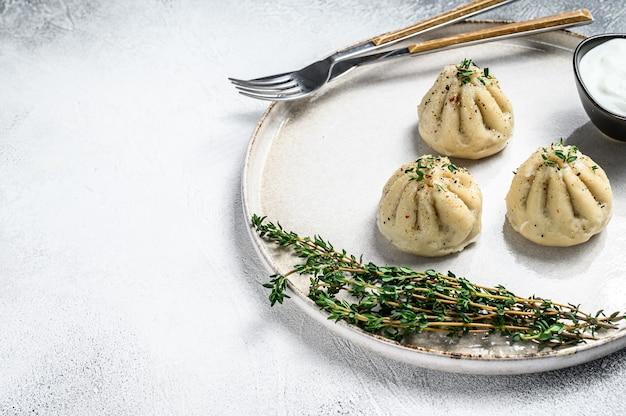 Gnocchi al vapore asiatici manti con carne macinata su un piatto.