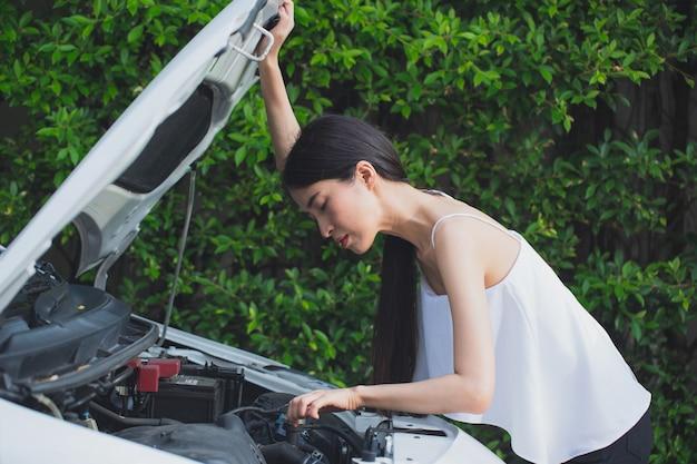 Donna stressata asiatica vicino all'automobile rotta che ritiene disperata