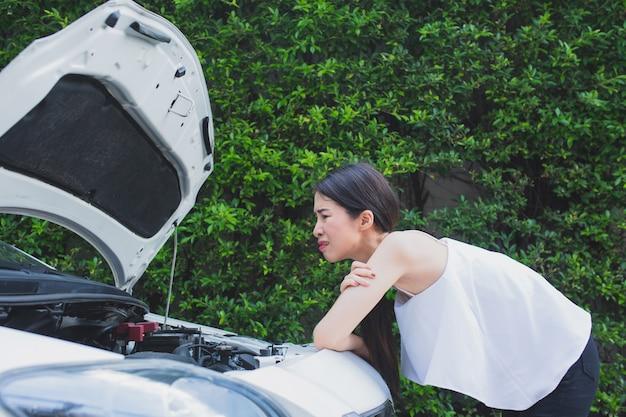 Donna stressata asiatica vicino all'automobile rotta