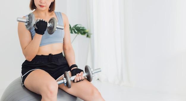 Esercizio di donna forte asiatica con manubri a casa