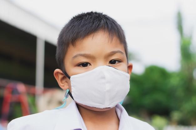 Ragazzo asiatico del bambino dell'allievo che porta la maschera del tessuto