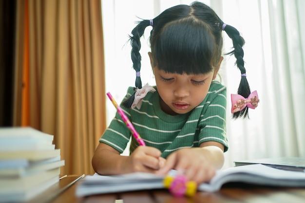 Ragazza asiatica del bambino dell'allievo che scrive sul libro di carta.