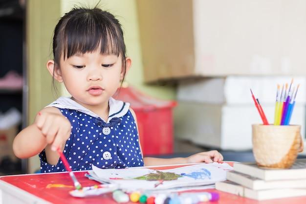 Studente asiatico che disegna e dipinge i colori sulla carta nella stanza.