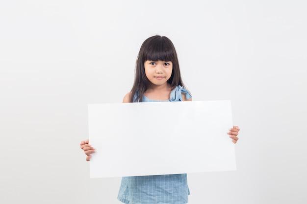 Ragazza asiatica dell'allievo che tiene un manifesto in bianco per testo
