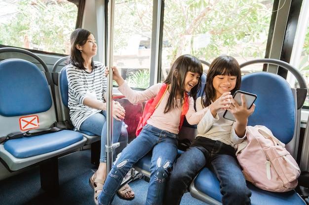 Studentessa asiatica che usa lo smartphone mentre guidano insieme un autobus pubblico sulla strada per la scuola