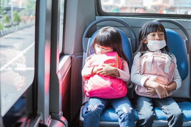 Studenti asiatici che vanno a scuola insieme con i mezzi pubblici