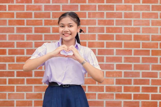 Sorridere felice del ritratto di gesto del segno del cuore di amore della mano dello studente asiatico.
