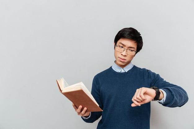 Studente asiatico guardando l'orologio.