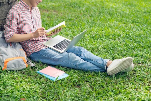 Studente asiatico che legge un libro mentre è seduto sull'erba verde