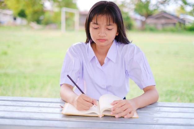 Studente asiatico studia fuori porta a scuola