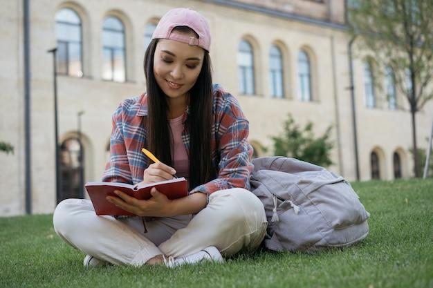 Studente asiatico che studia la preparazione all'esame seduto sull'erba nel campus universitario