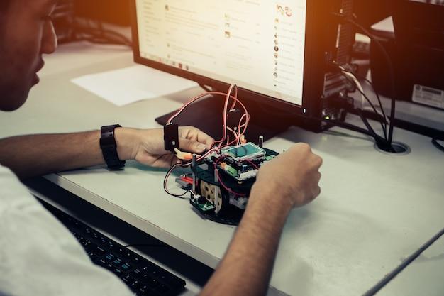Studente asiatico che pensa e apprende stem educazione alla robotica per creare progetti basati