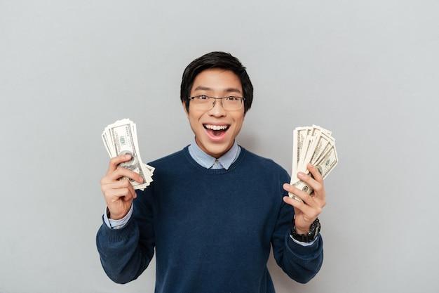 Studente asiatico con soldi. guardando la telecamera.