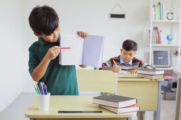 Uno studente asiatico che studia in classe e presenta la sua pagina del libro bianco per il mock up
