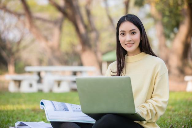 Gli studenti asiatici utilizzano computer portatili e tablet per lavorare e studiare online nel giardino di casa durante l'epidemia di coronavirus e mettere in quarantena a casa