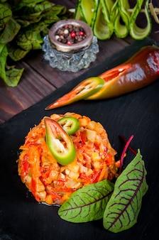 Stile asiatico saltato in padella per cucinare verdure calde saltate su ardesia, superficie in legno, melanzane, peperoncino, cetriolo