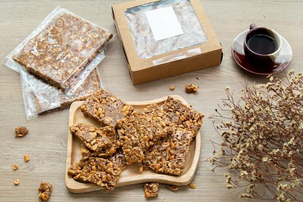 Spuntini dolci asiatici, gustose noci tagliate miste e caramello su fondo di legno luce naturale