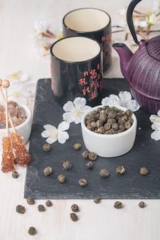 Servizio da tè asiatico con tè verde essiccato e zucchero