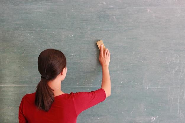 L'insegnante asiatico cancella sulla lavagna con la gomma del bordo in aula