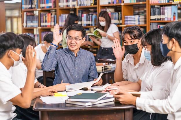Insegnante asiatico che alza la mano e dà lezione a un gruppo di studenti universitari per rispondere alla domanda nella biblioteca e in aula dell'università