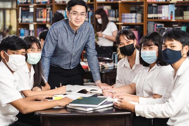 Insegnante asiatico in piedi con un gruppo di studenti universitari seduti in biblioteca e in aula istruzione universitaria
