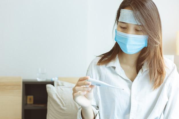Influenza del coronavirus adolescente asiatica infettata guardando ansiosamente il termometro digitale che sarebbe stato infettato dal virus covid-19