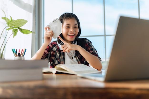 Ragazza adolescente asiatica che indossa le cuffie che impara la lingua online, usando il laptop, guardando lo schermo, facendo compiti scolastici a casa, scrivendo appunti, ascoltando lezioni o musica, educazione a distanza