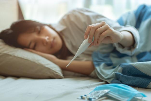 Adolescente asiatica affetta da influenza covid-19 malata a letto a causa di una pandemia di virus corona, misura ansiosamente la temperatura corporea di controllo con un termometro digitale.