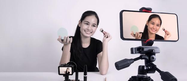 Una giovane donna asiatica si siede davanti alla telecamera e trasmette in diretta come influencer blogger di bellezza